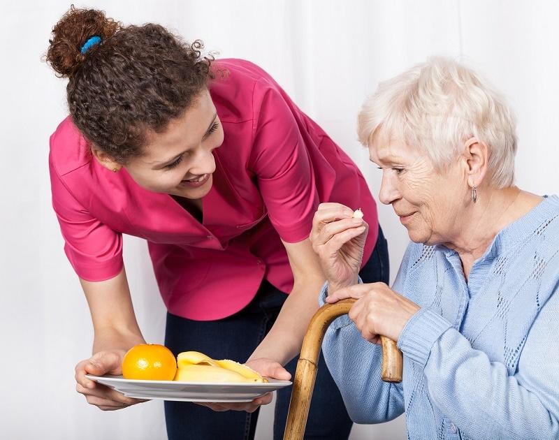 Home care caregiver serving fruit to an elder woman