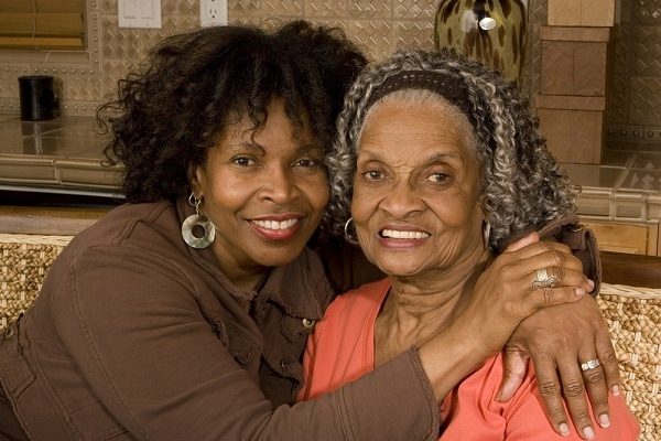 Elderly african american women at home with her caring daughter